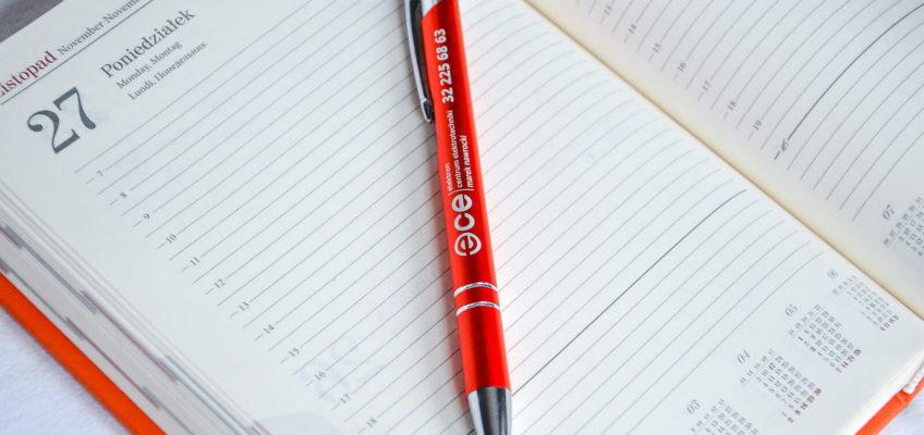 Gadżet reklamowy - pomarańczowy długopis z nadrukiem ECE i numerem telefonu